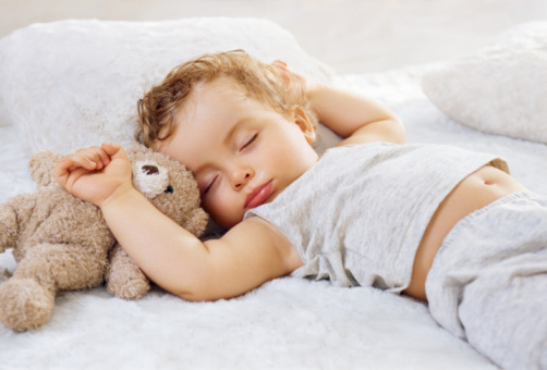Sleeping baby boy arms raised up with a Teddy bear on a white blanket